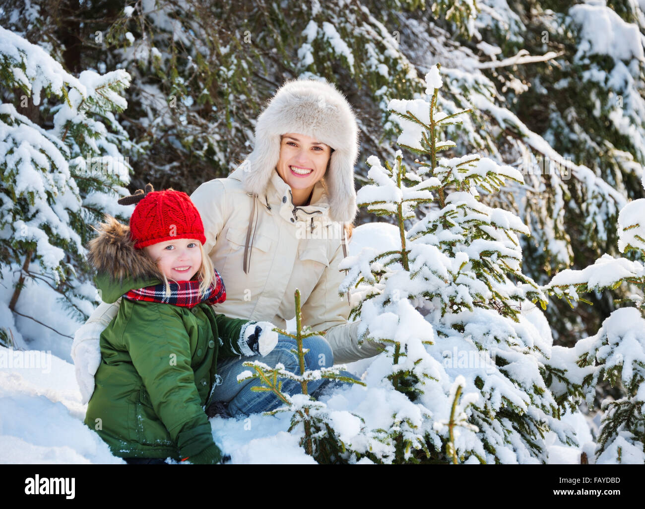 Winter outdoors can be fairytale-maker for children or even adults. Happy mother and child outdoors among snowy - Stock Image