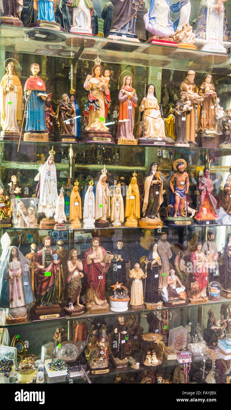 statues and other devotional objects in the window of a specialized shop, lisbon, portugal - Stock Image