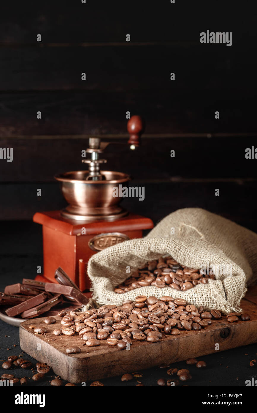 Still life of coffee beans in jute bags with coffee grinder on dark background. Copyspace on top. - Stock Image