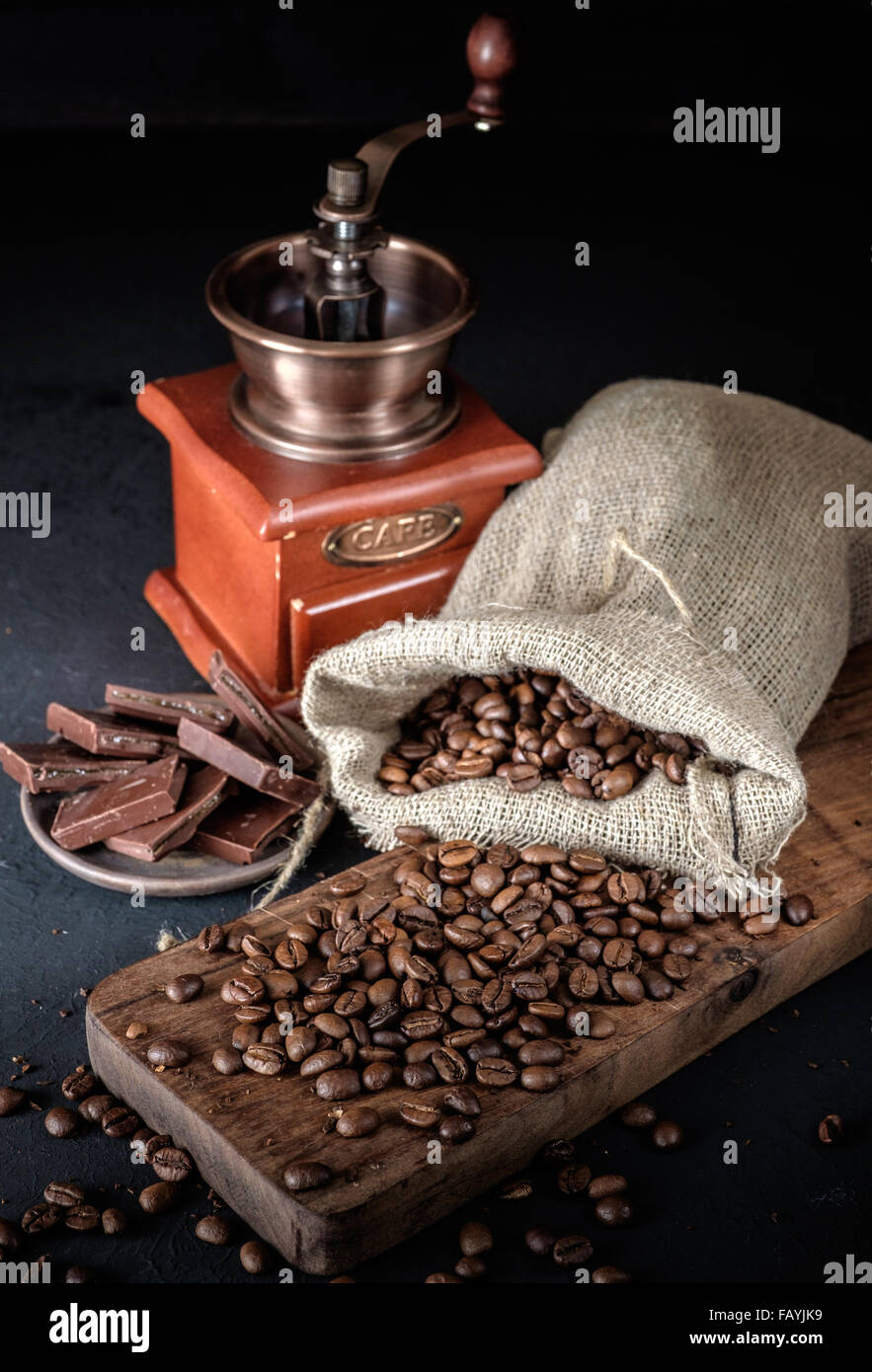 Still life of coffee beans in jute bags with coffee grinder on dark background. - Stock Image