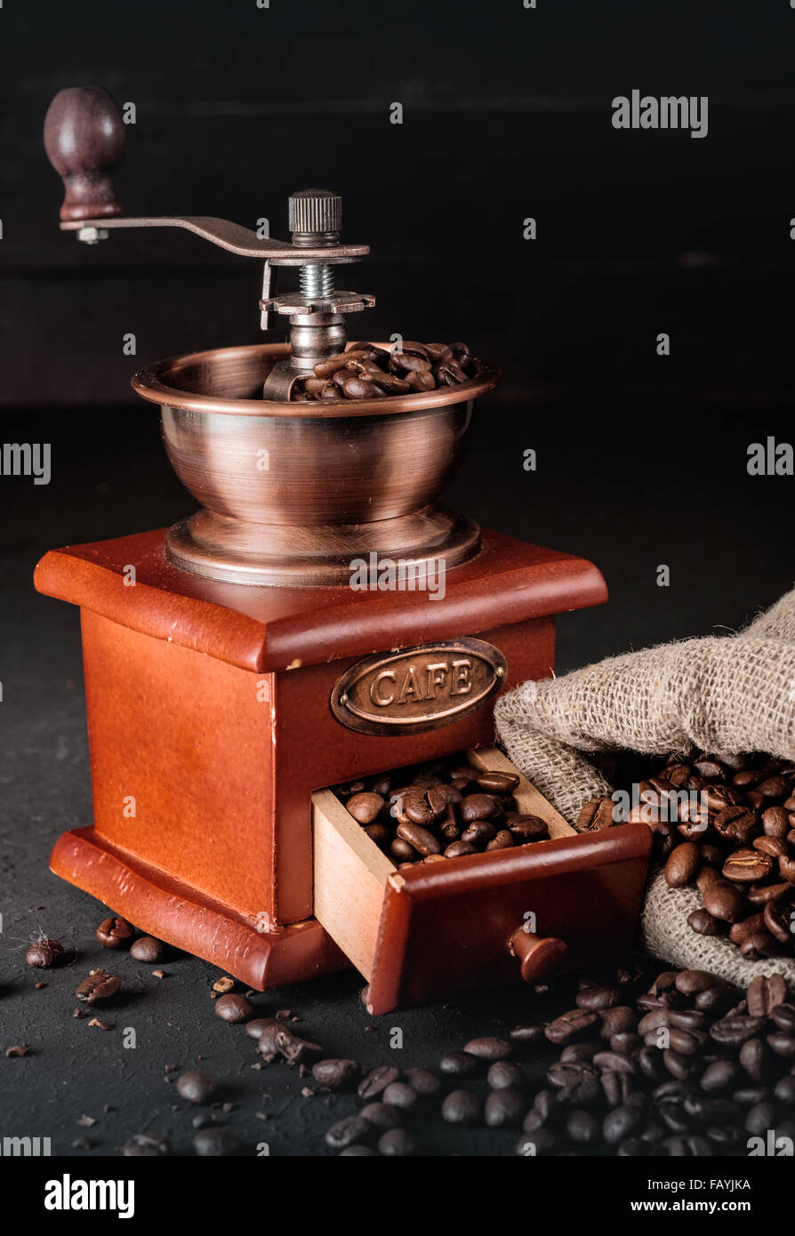 Coffee beans in jute bags with coffee grinder on dark wooden background. - Stock Image