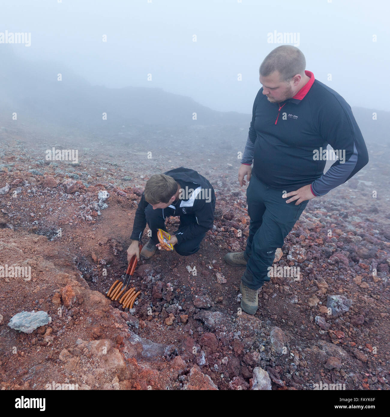 Cooking hot dogs in the steaming earth after Eyjafjallajokull Volcanic eruption,   Fimmvorduhals, Iceland - Stock Image