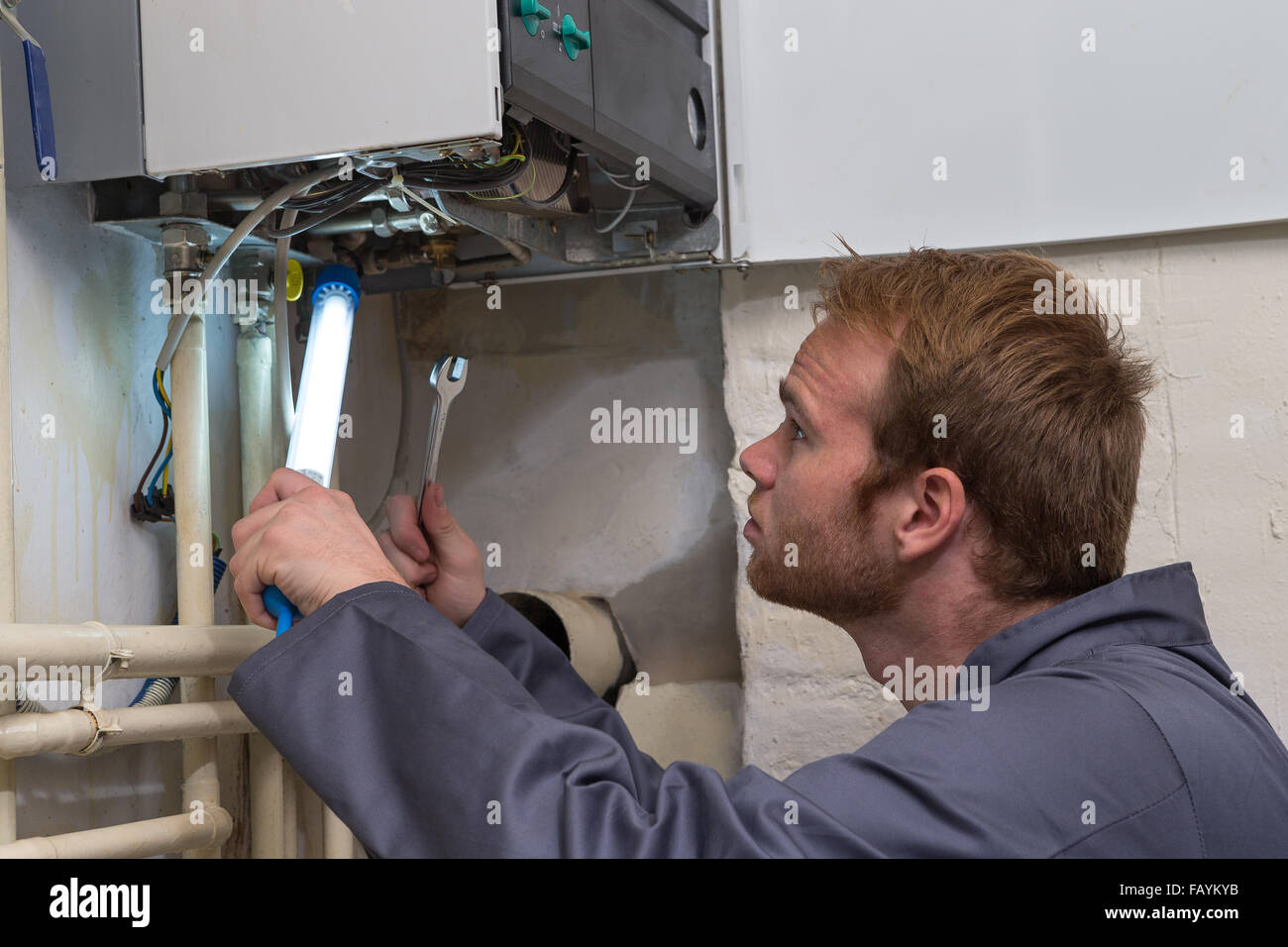 Technician controlling the heating system - Stock Image