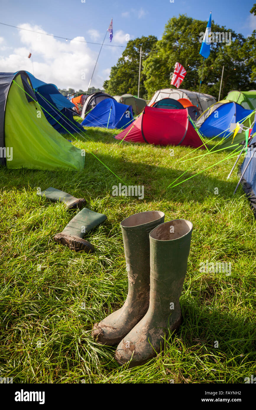 A pair of muddy wellington boots at a British music festival campsite. Shallow depth of field with selective focus - Stock Image