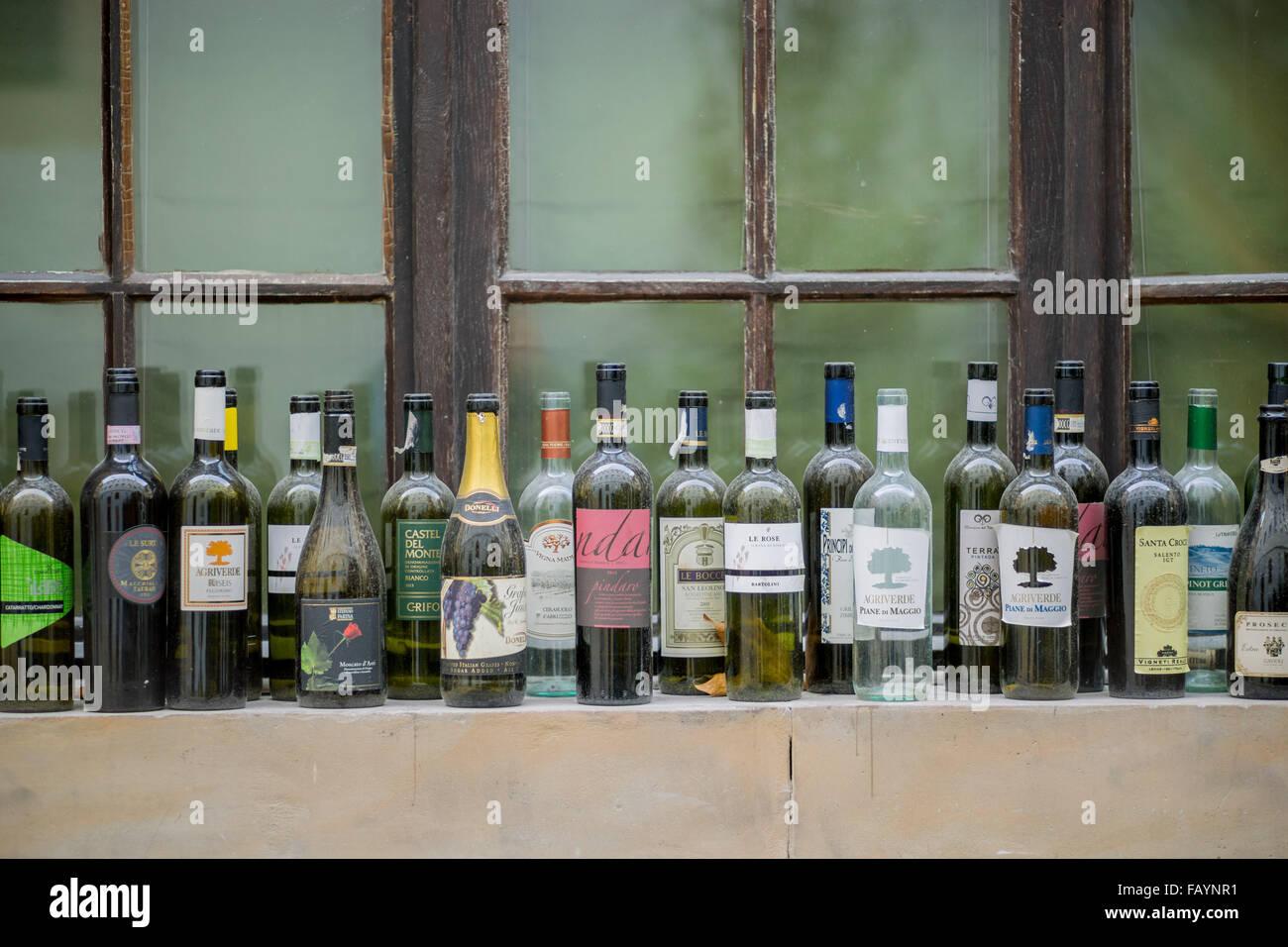 Empty wine bottles standing on the windowsill - Stock Image