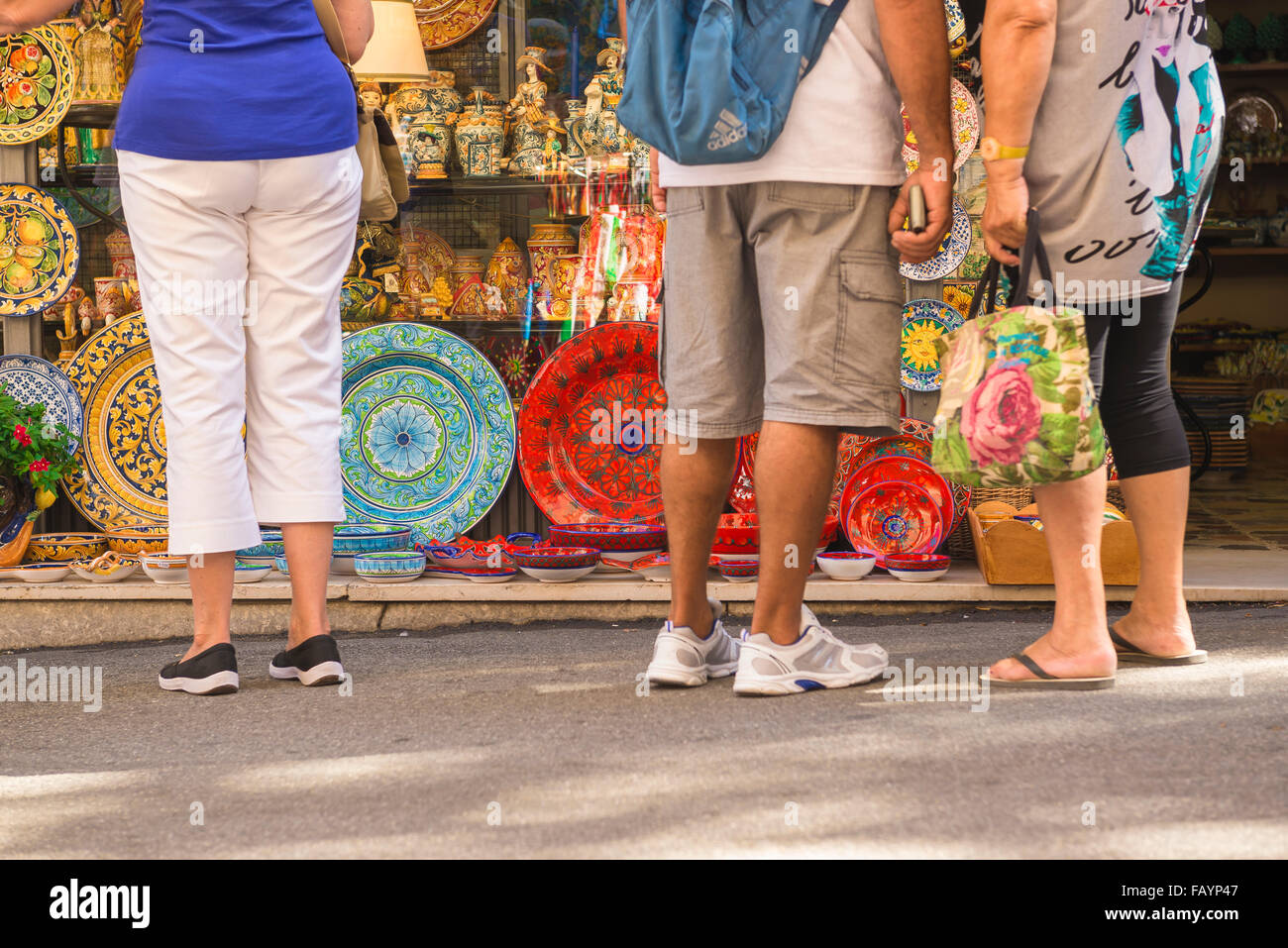 Tourists shopping Sicily, rear view of tourists in a Taormina street pausing to look at colourful ceramic plates - Stock Image