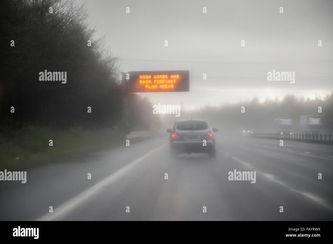Smart motorway warning sign in rain for 'High winds and rain forecast - plan ahead' - Stock Image
