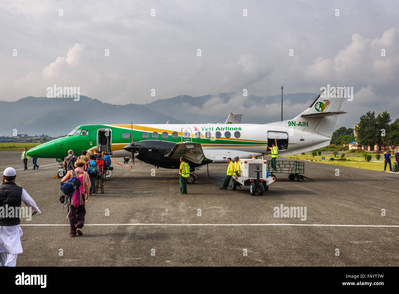 People board a small airplane flying from Pokhara to Kathmandu. - Stock Image
