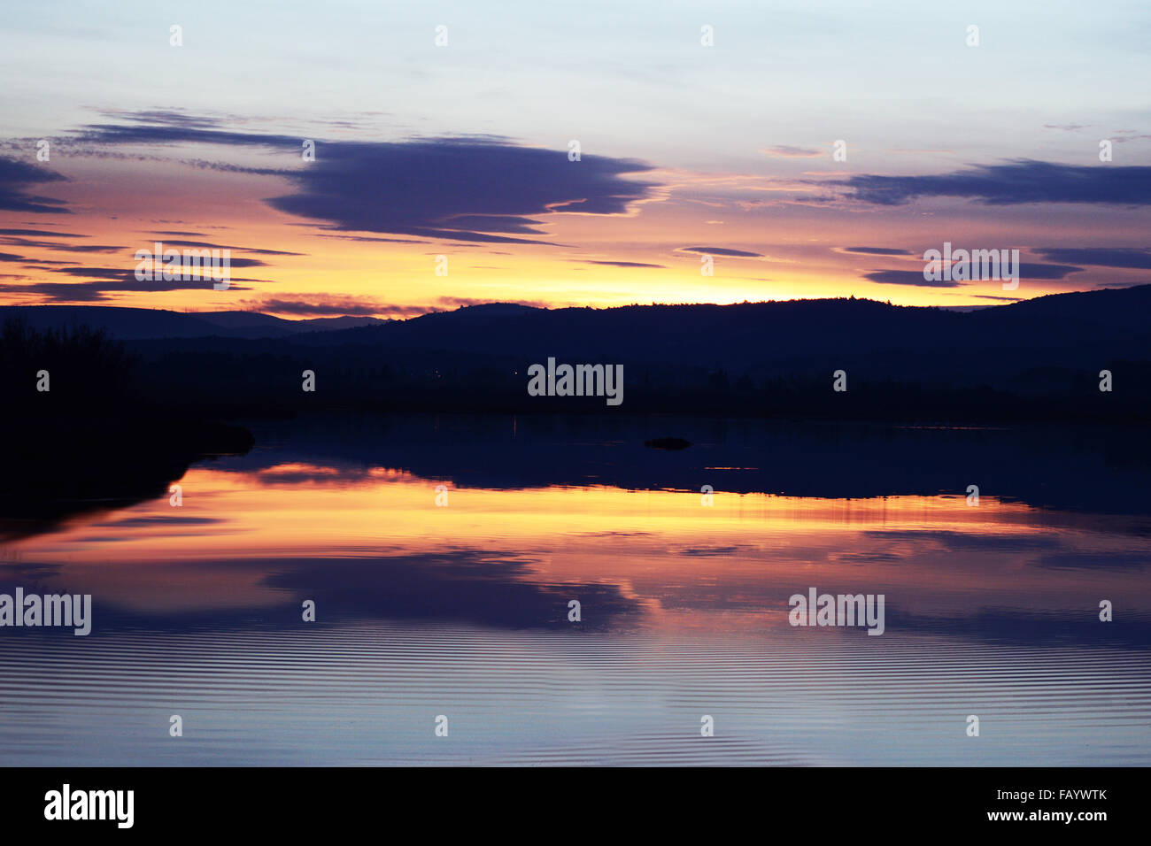 Setting sun over mountains with colours reflected in a lake with gentle ripples on the water evoking a scene of - Stock Image