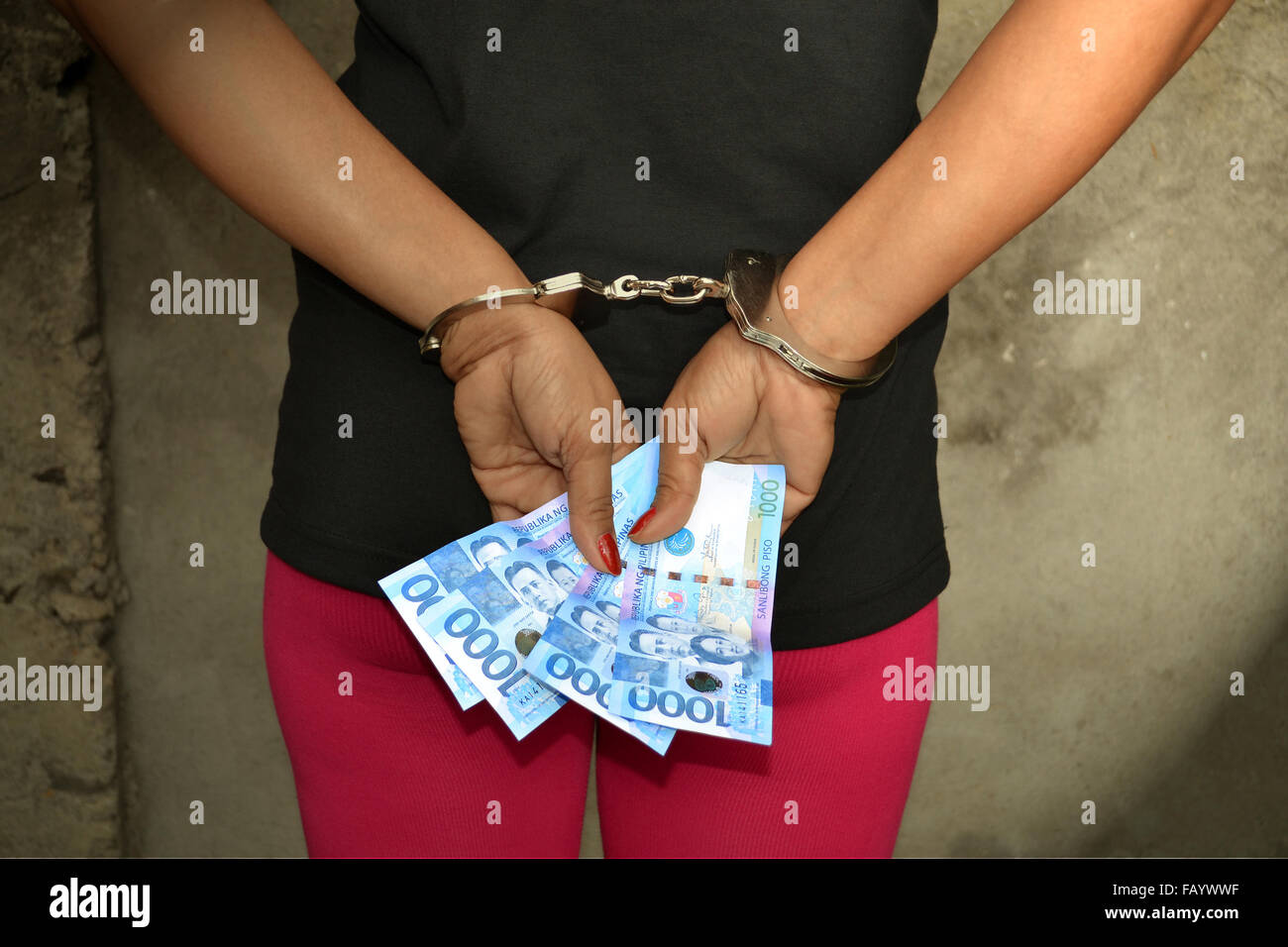 Female thief cuffed hands with Filipino money in her hands - Stock Image