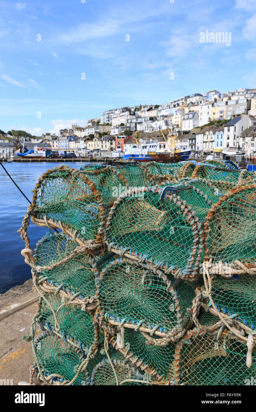 Lobster pots on the New Quay, Brixham, Devon, on a glorious summer's day; the town rises in the background over - Stock Image
