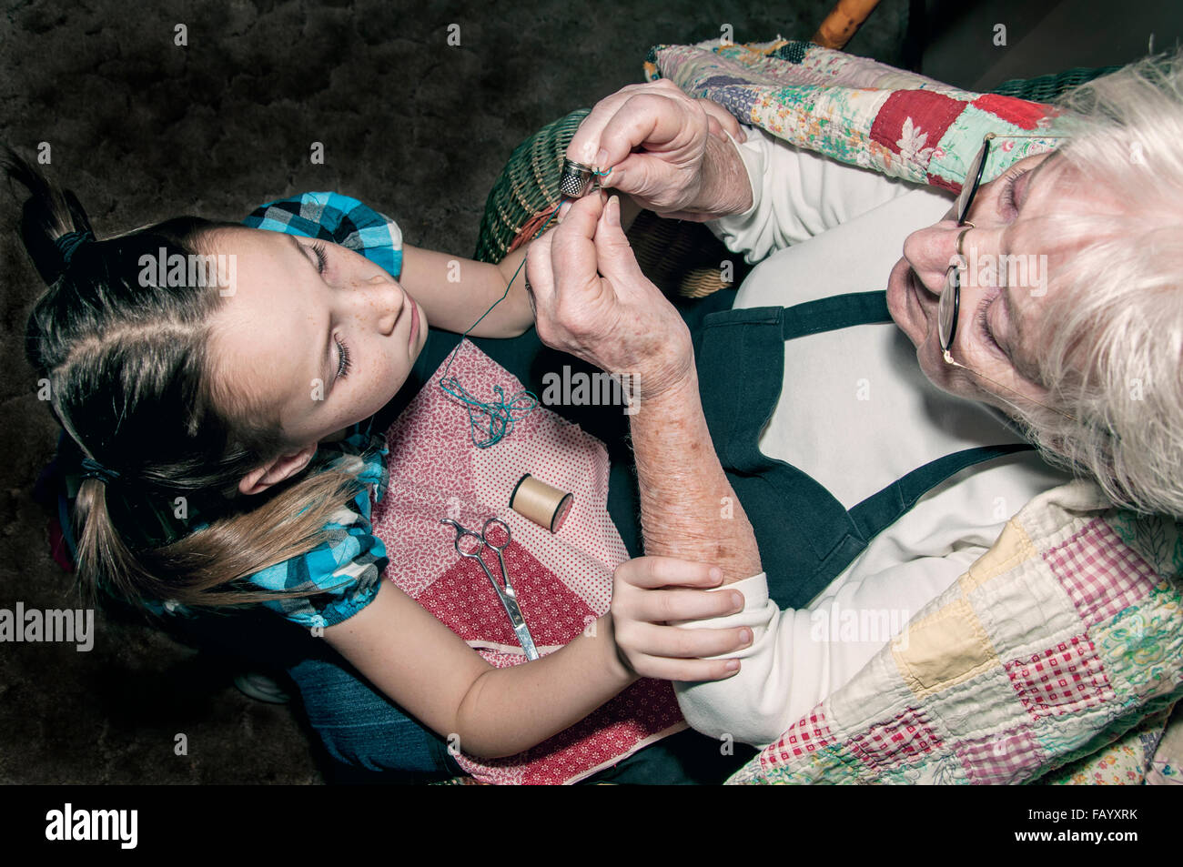 Girl holding grandmothers hands steady to thread needle - Stock Image