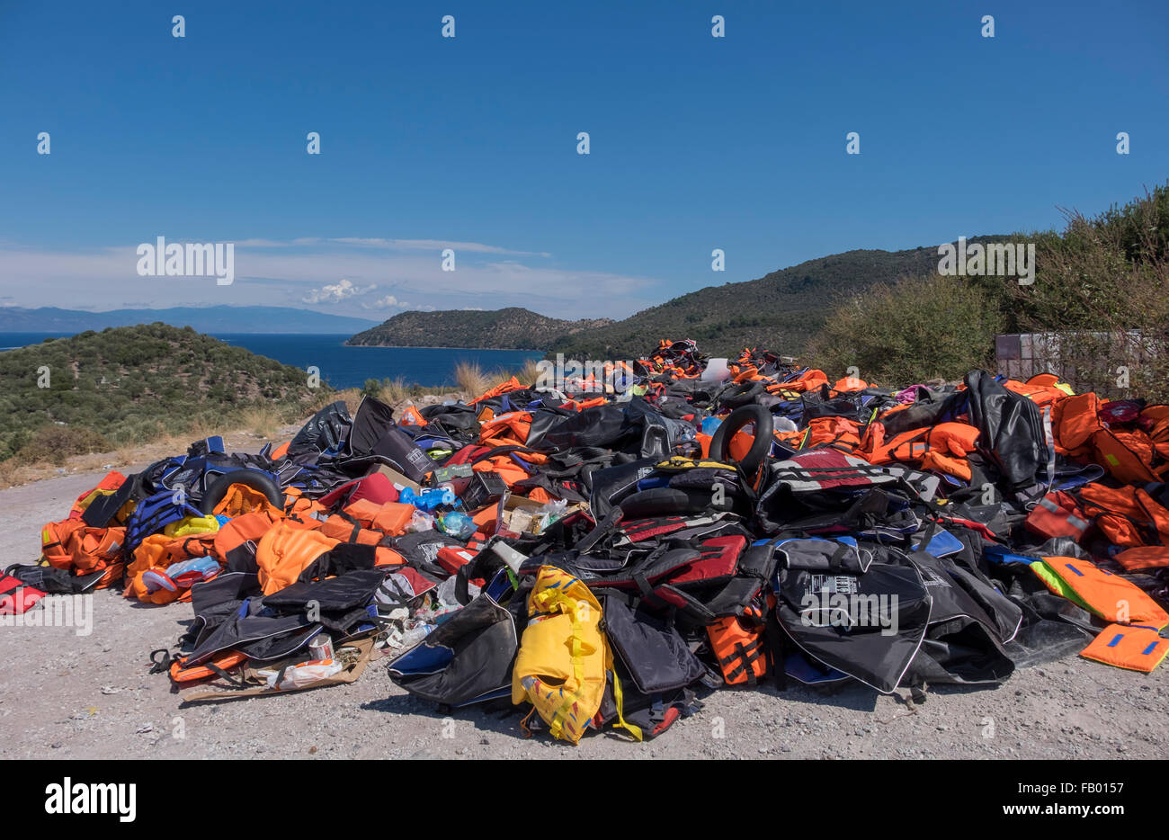 A mountain of life vests left behind by refugees crossing into the Greek island of Lesvos from Turkey (in the distance). - Stock Image