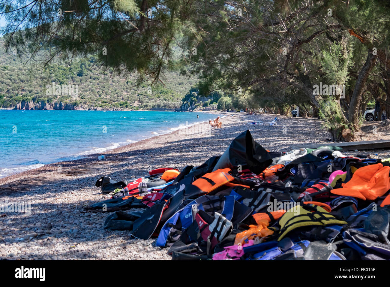Cast off life jackets piled up on a beach from refugees landing on the island of Lesvos after crossing from Turkey. - Stock Image
