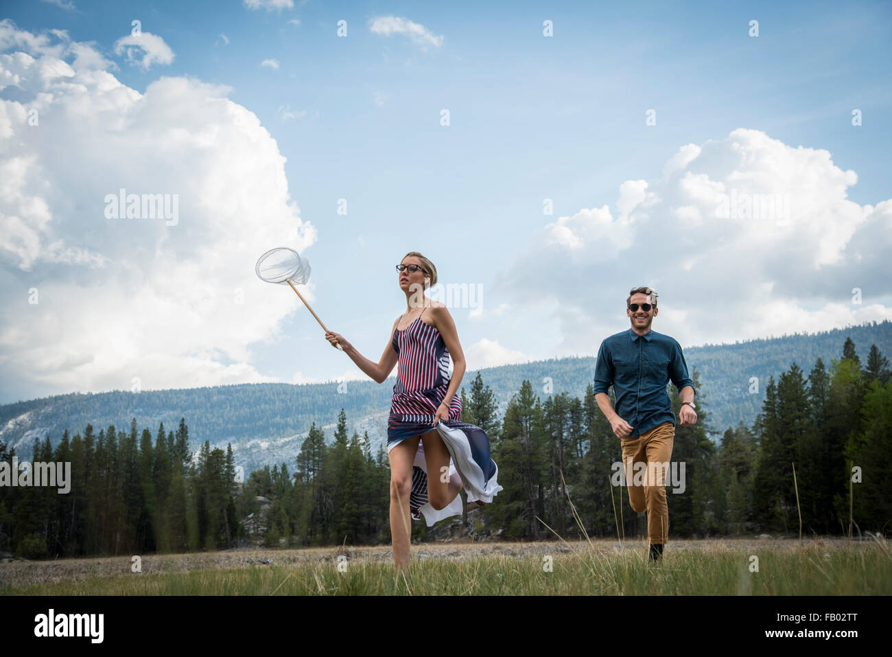 Young couple running  through  a meadow  catching butterflies. - Stock Image