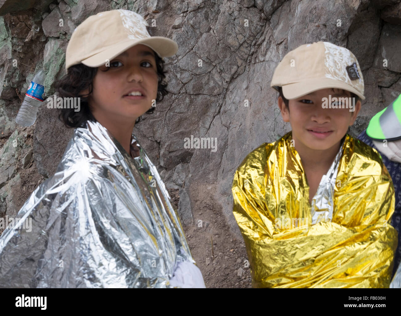 Two Afghani refugee children smile as they get warm in hats and blankets after crossing from Turkey to Lesvos, Greece. - Stock Image