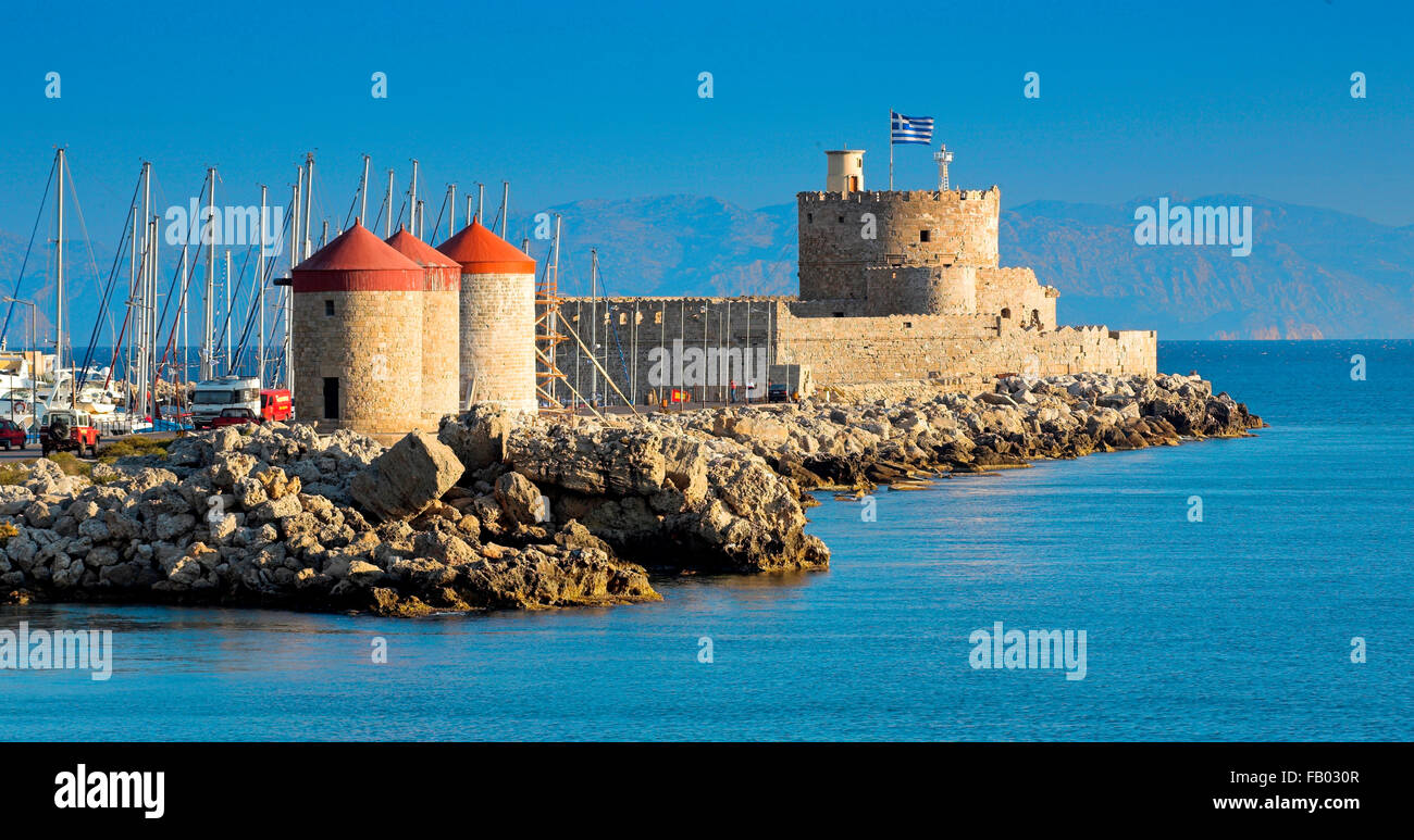 The Castle and old windmills at the enterance to Mandraki harbour in Rhodes, Greece - Stock Image
