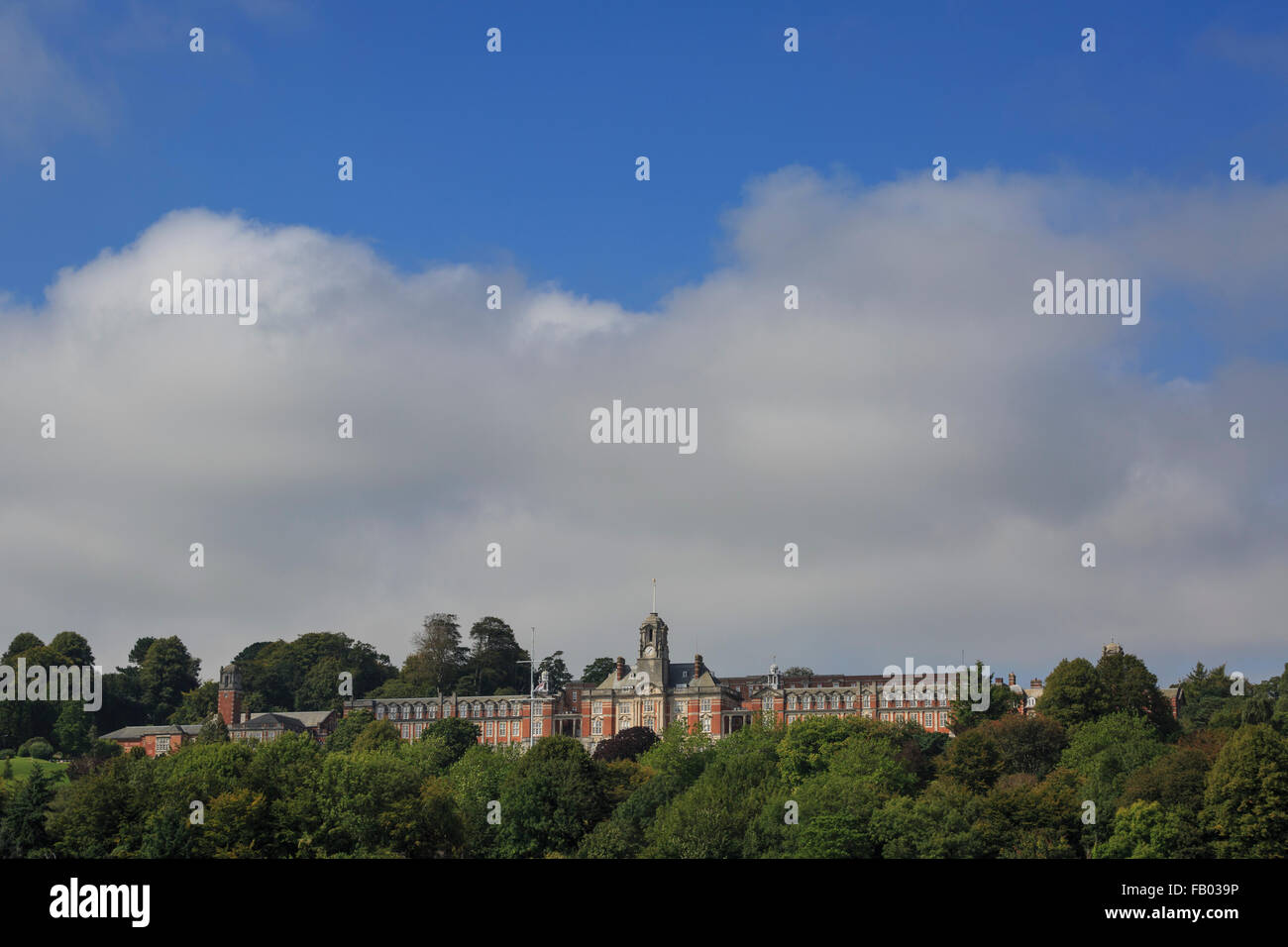 The Britannia Royal Naval College (HMS Dartmouth) dominates the skyline above Dartmouth, Devon, on a partly-cloudy Stock Photo