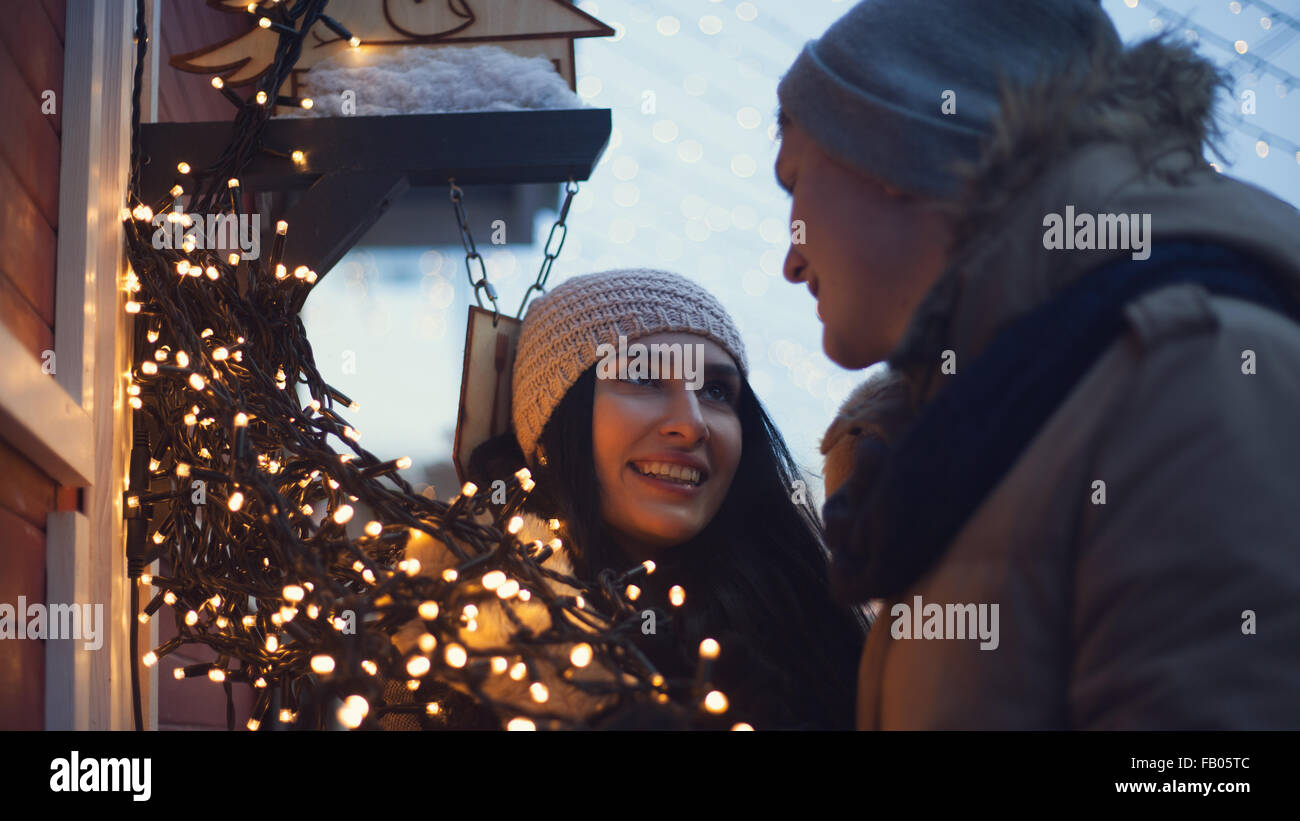 Young couple have fun with christmas lights during walks on christmas market - Stock Image