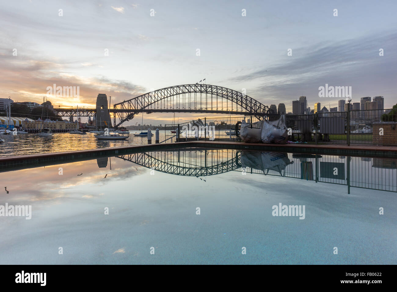 Beautiful sunrise scene at Sydney Harbour Bridge with dramatic sky colour and reflection - Stock Image