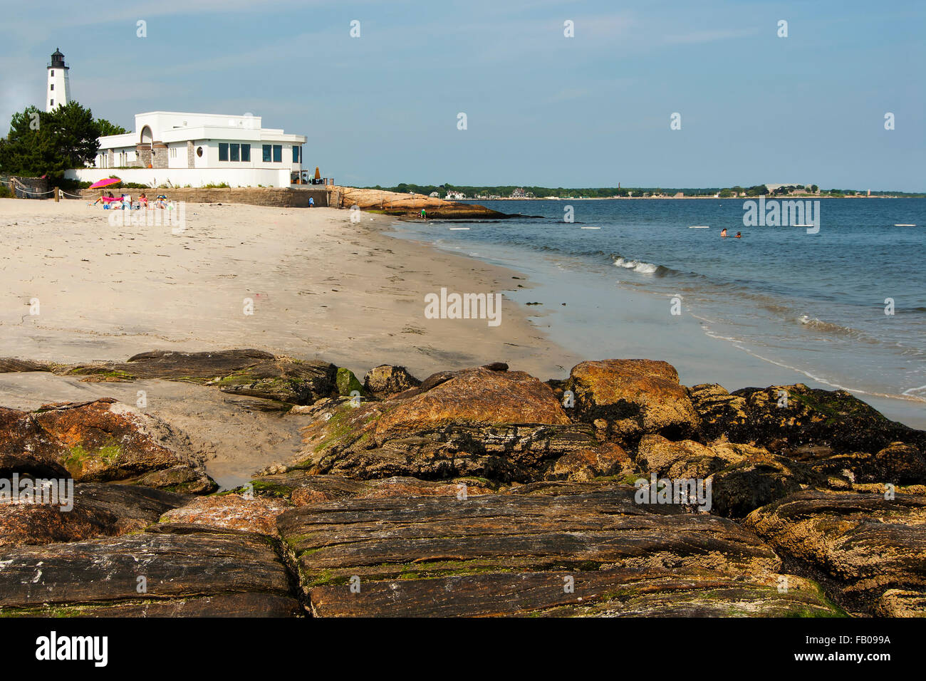 Empty beach surrounds New London Harbor lighthouse in Connecticut during low tide on a quiet warm summer day. - Stock Image