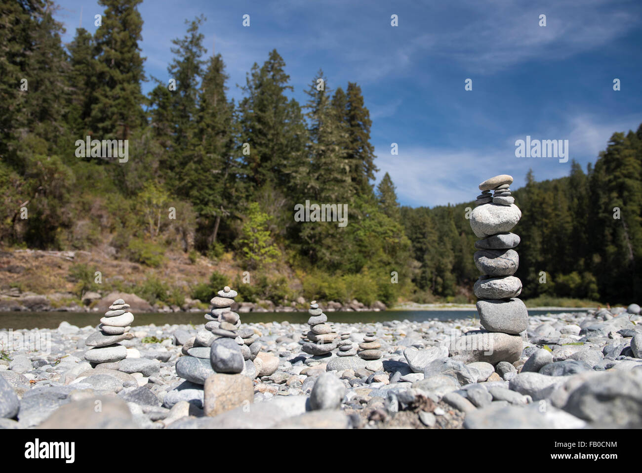 Rock cairns on the Smith River riverbed at Jebediah Smith Redwoods State Park in Northern California, USA. - Stock Image