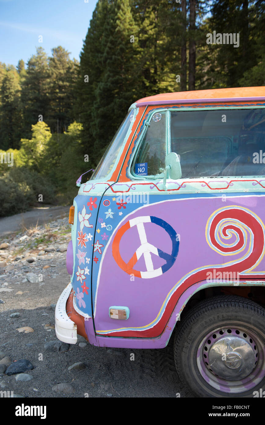 A colorful Volkswagen bus painted in a psychedelic hippie style at Jebediah Smith Redwoods State Park in Northern - Stock Image