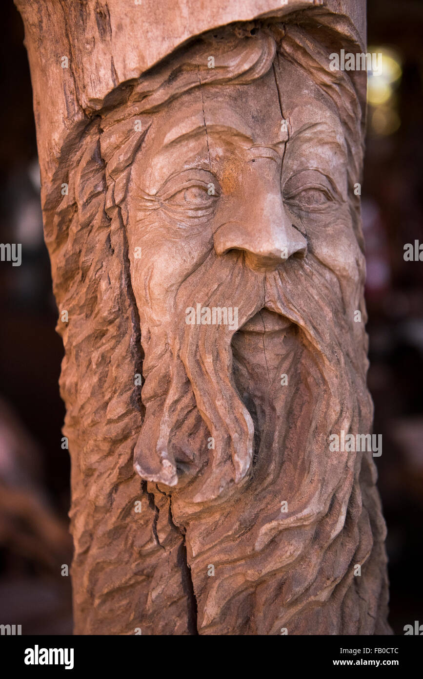 A wooden carving of an old man's face in a pole at It's A Burl Gallery, a gallery, wood yard, and shop in - Stock Image