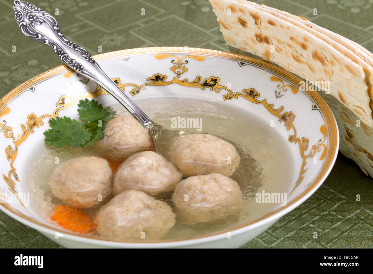 A traditional Ashkenazi Jewish soup with bolls, made from a mixture of matzah meal, eggs, water, and fat, boiled - Stock Image