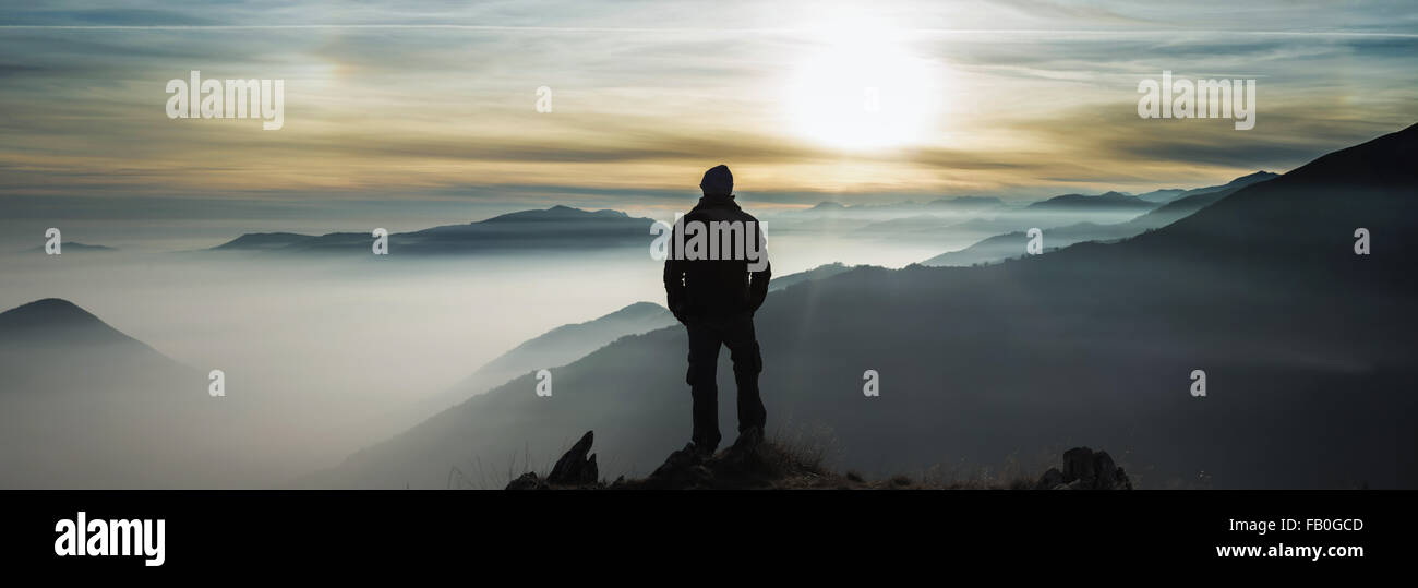 Man watching mountains clouds from a peak in the Alps - Stock Image