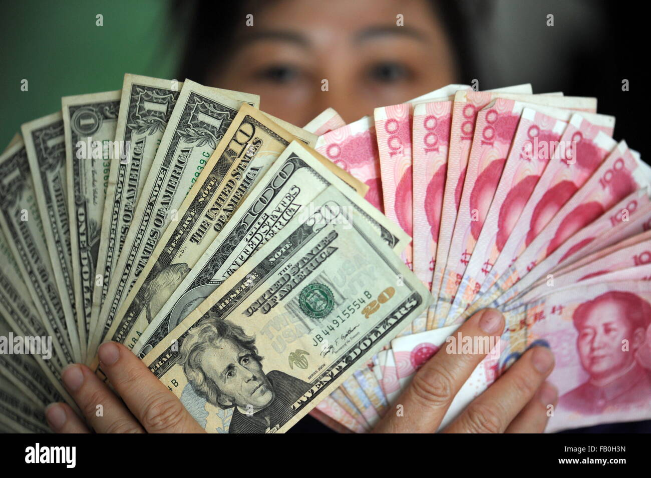 Qionghai, China's Hainan Province. 7th Jan, 2016. A residents shows China's RMB and US dollar banknotes - Stock Image