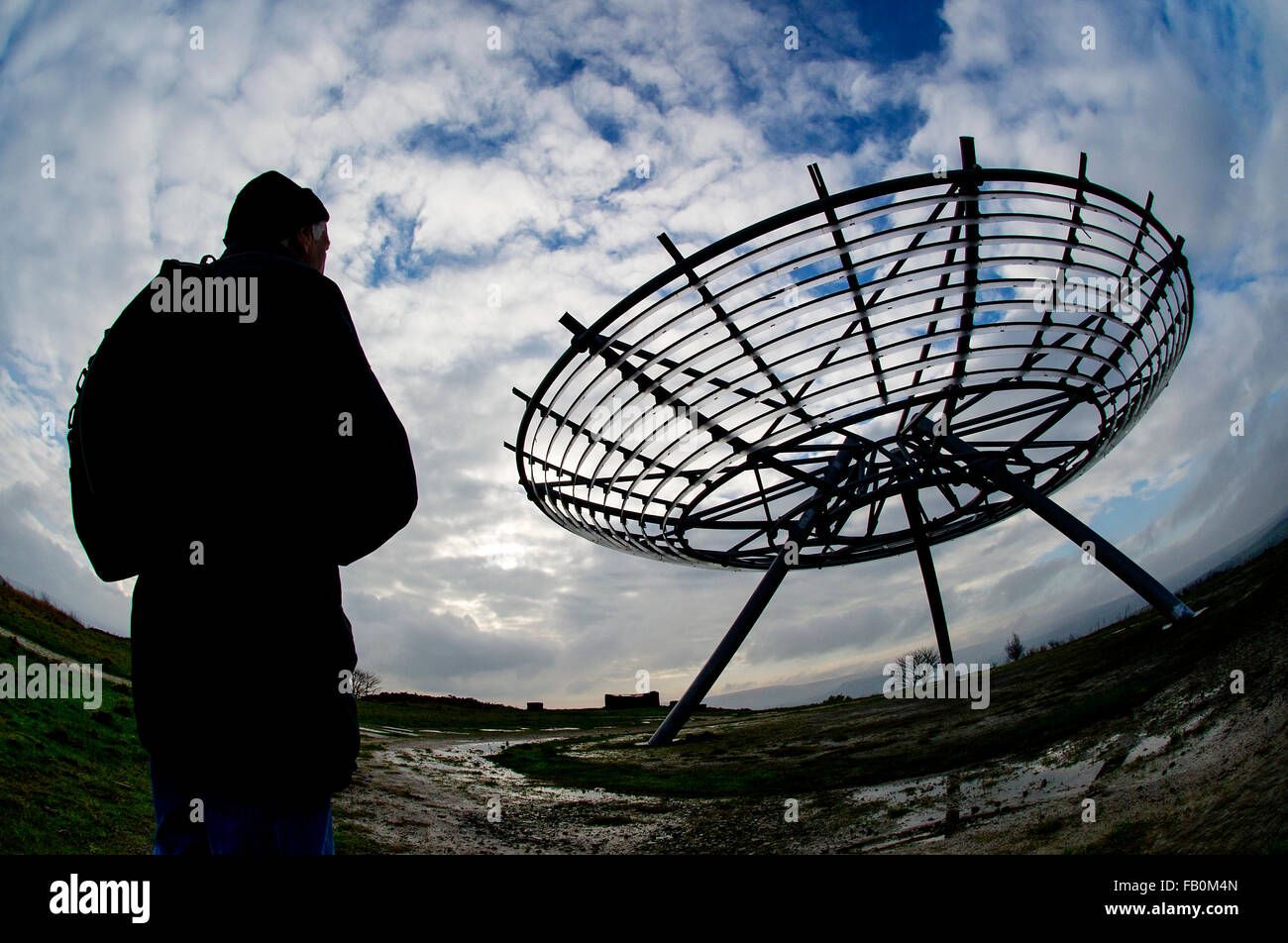 A walker stops to admire the view of The Halo panopticon on the hills above Haslingden, Lancashire as bad weather - Stock Image