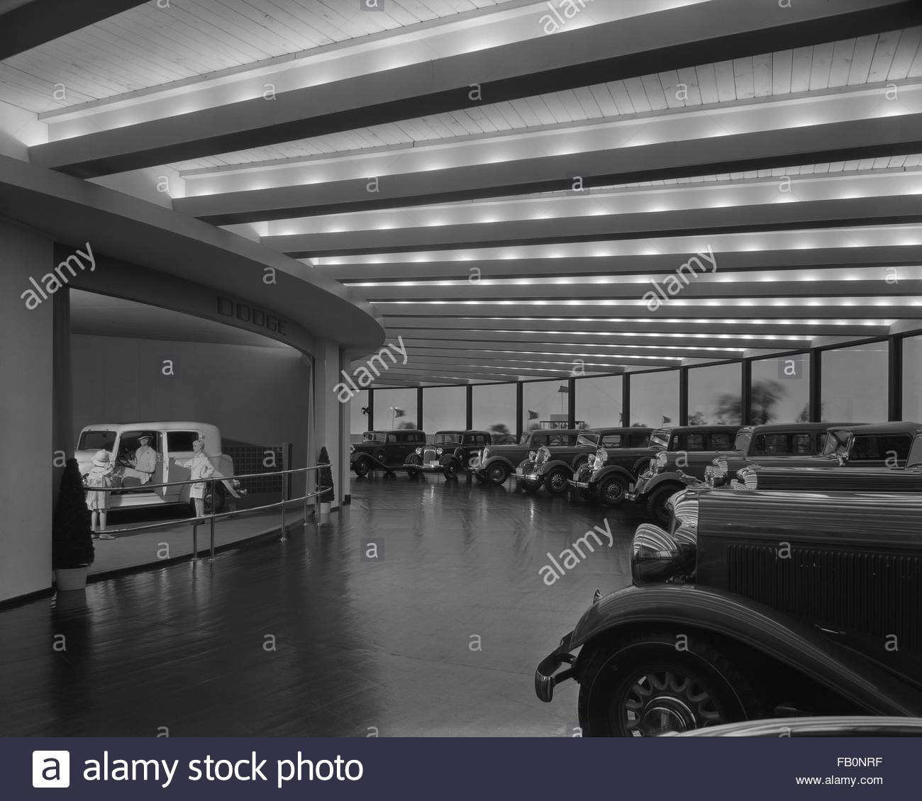 Interior, Dodge showroom with  cars lined along the wall and exhibit with a car and mannequins. Chrysler Motors - Stock Image