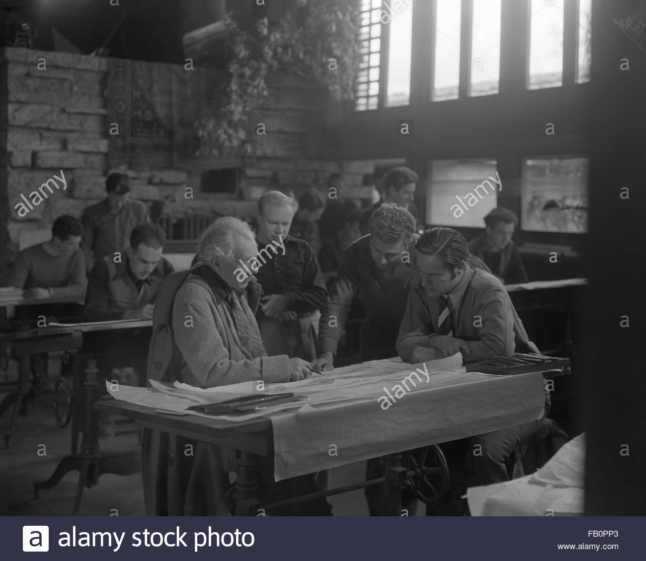 Portraits of Frank Lloyd Wright and others at Taliesin East [graphic], 1937 Dec. Frank Lloyd Wright at a drafting - Stock Image