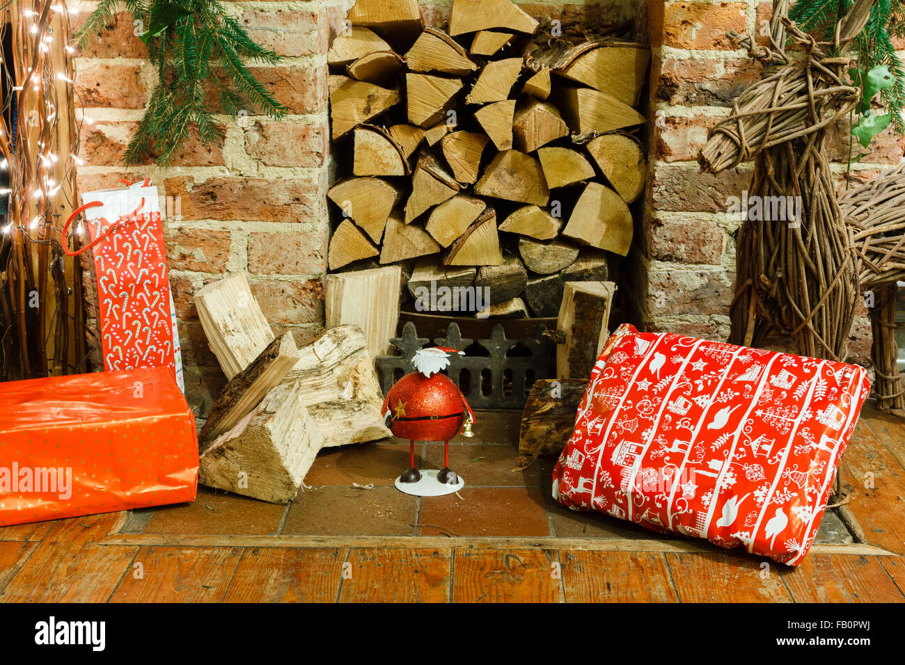 Christmas gifts and presents by a fireplace in an English living room - Stock Image