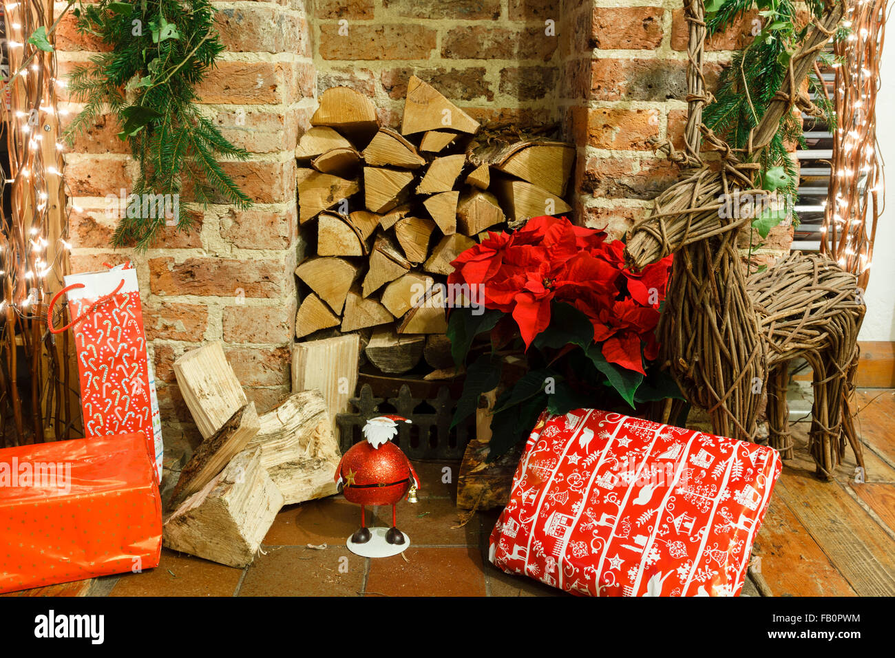 Christmas gifts and presents by a fireplace in an English living room, UK - Stock Image