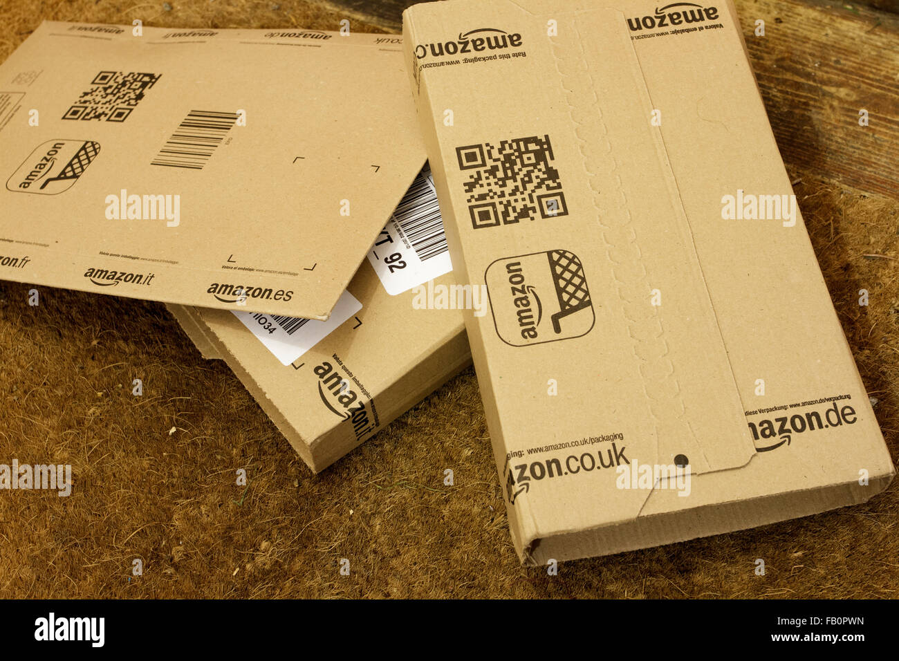 Amazon delivery boxes on the floor by the front door of house in England, UK - Stock Image