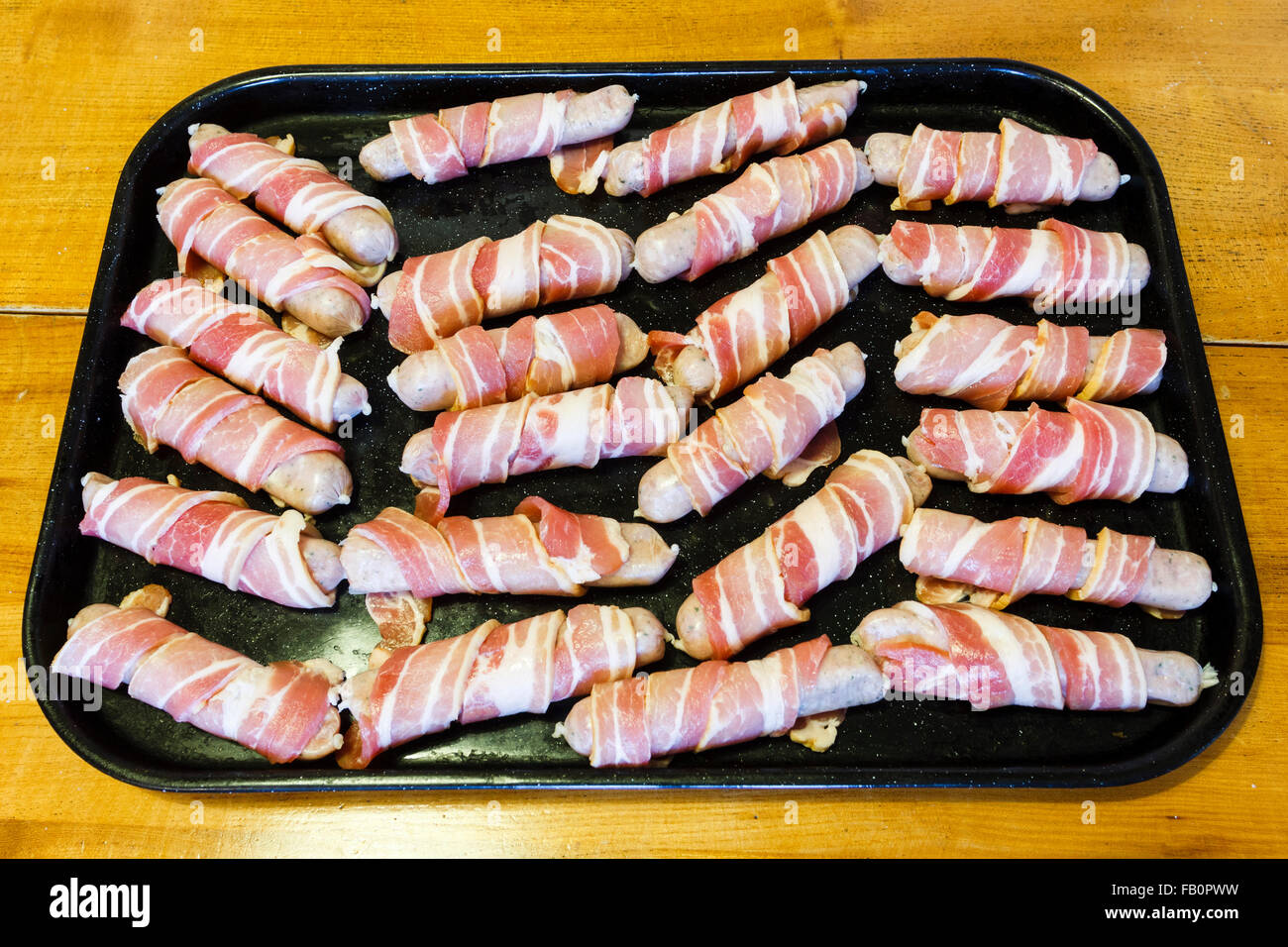 Traditional Christmas food of sausages wrapped in streaky bacon, on a baking tray. England, UK - Stock Image
