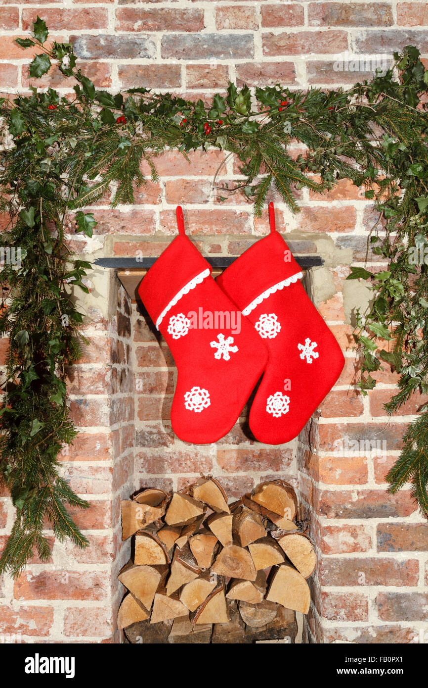 Christmas stockings hanging over a log store/fireplace decorated with holly and ivy sprigs - Stock Image