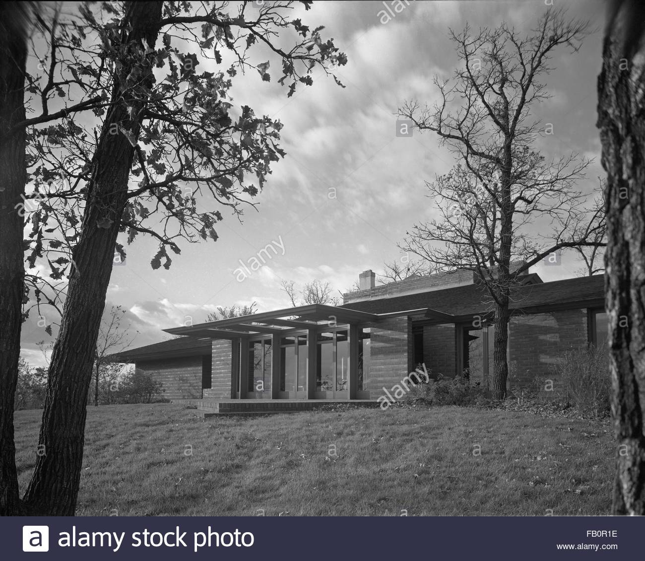 Malcom E. Willey residence in Minneapolis (Minn.), 1937 Dec. Exterior of home with trees framing the image. - Stock Image