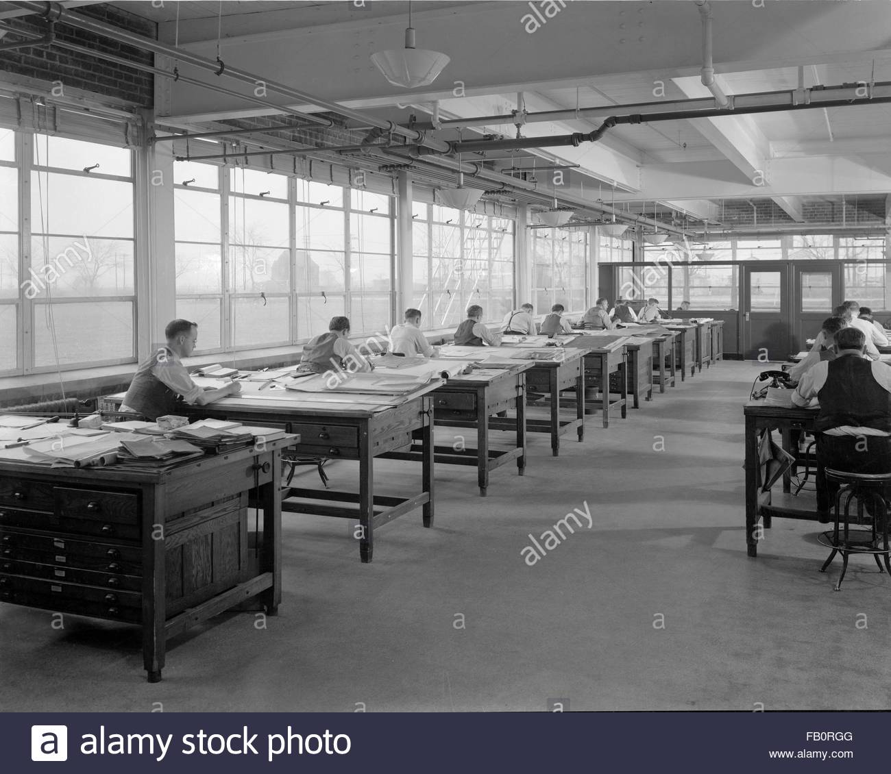 Toledo Scale plant in Ohio, 1939 Dec. 27. Rows of draftsmen working at their desks. - Stock Image