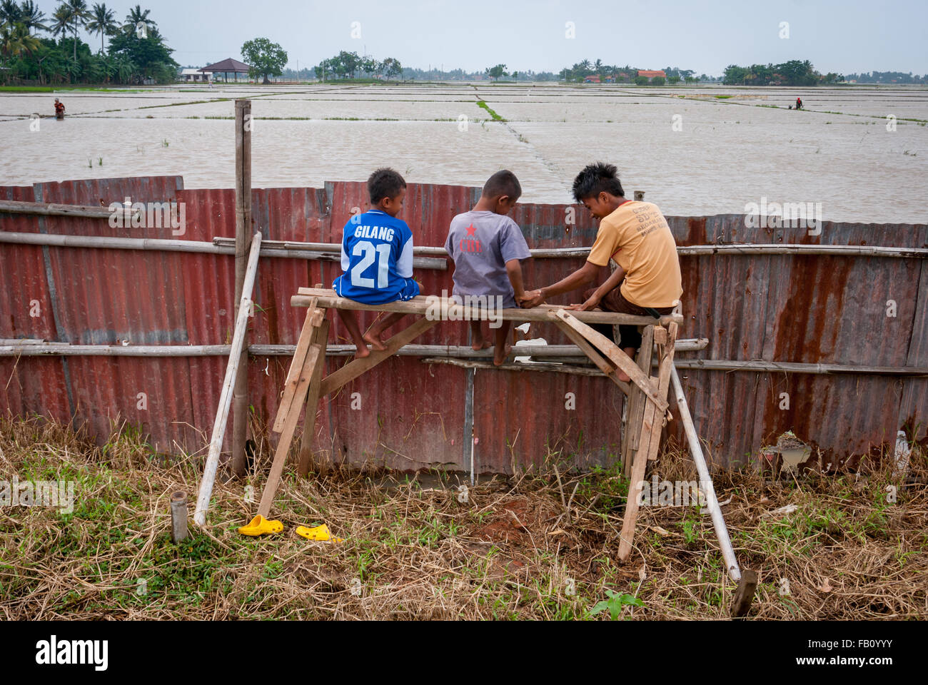 Children sit on wooden platform behind zinc fence. - Stock Image