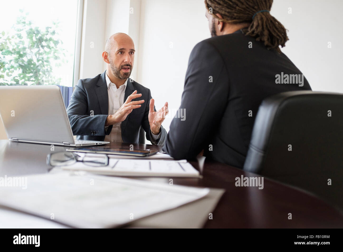 Two businessmen having discussion at desk in office - Stock Image