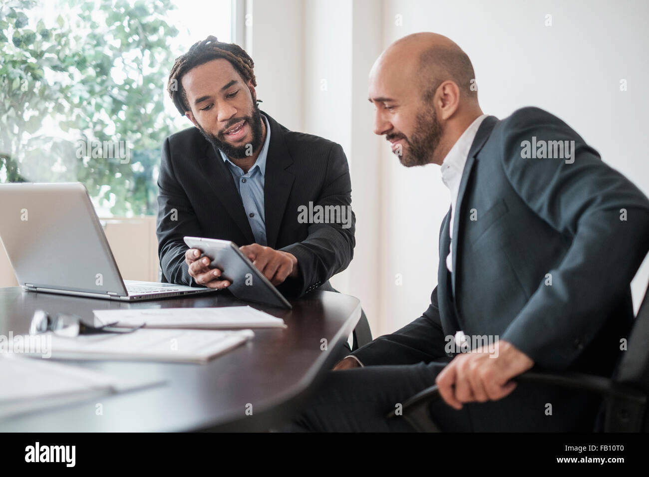 Two businessmen working with digital tablet by desk in office - Stock Image