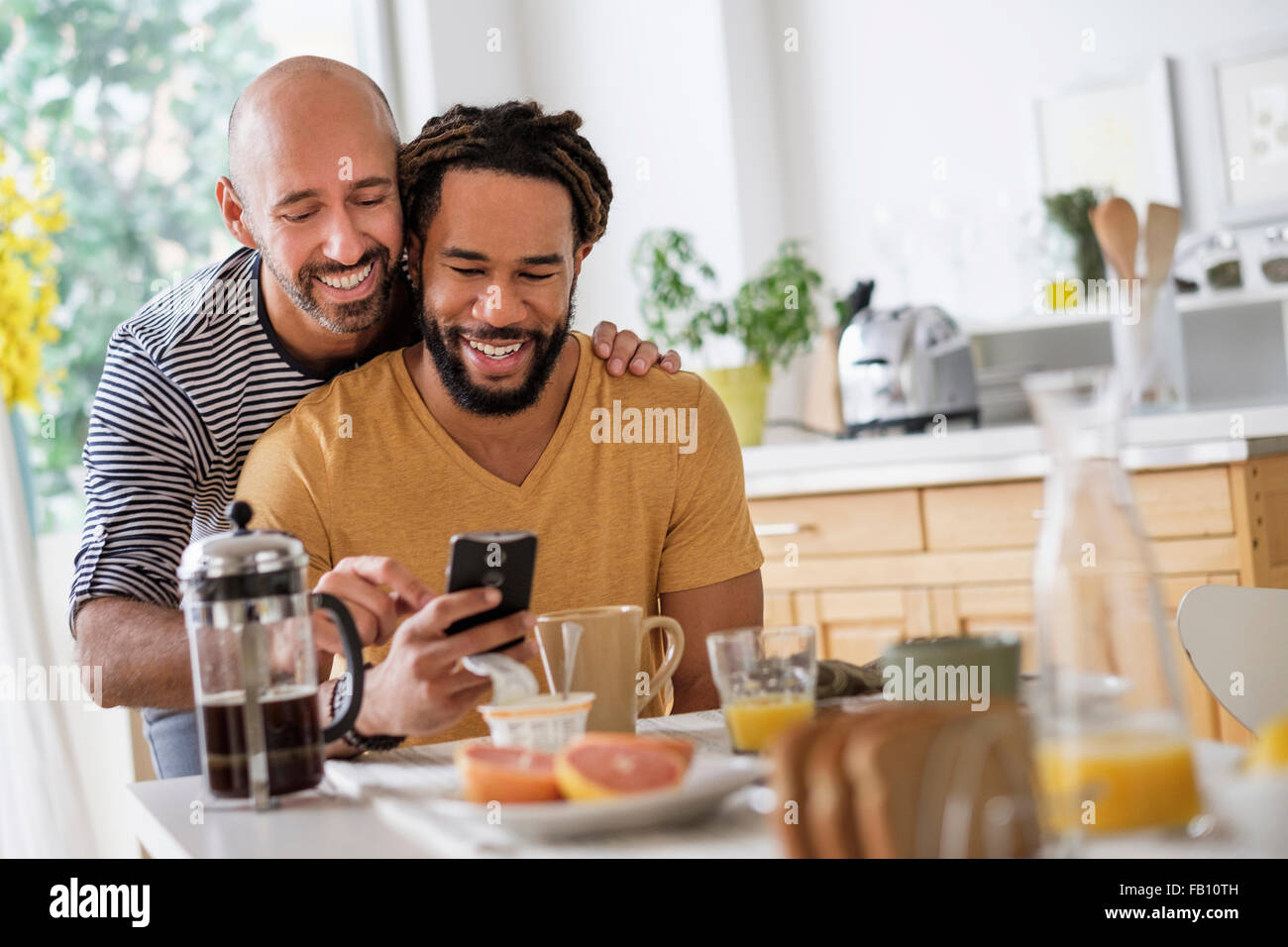Smiley homosexual couple using smart phone at dinner table Stock Photo