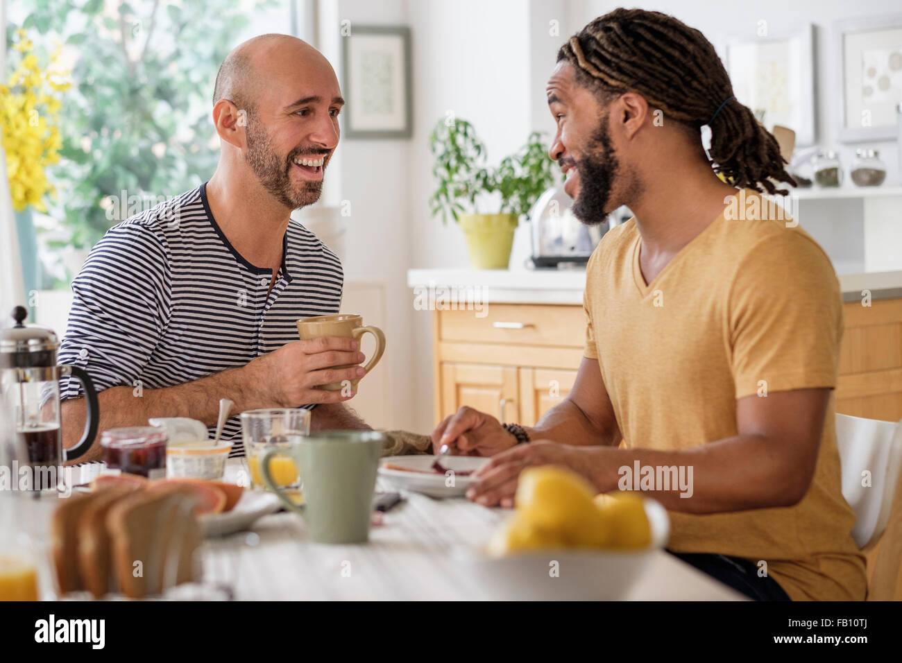 Smiley homosexual couple having breakfast in kitchen - Stock Image