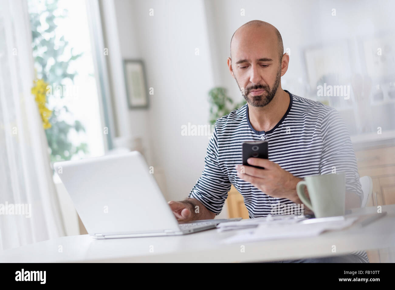 Man working with laptop and holding smart phone at table - Stock Image
