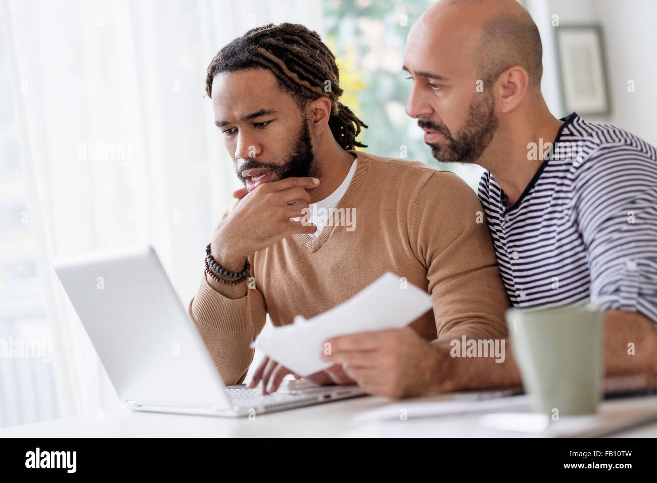 Two men working with laptop at table at home - Stock Image