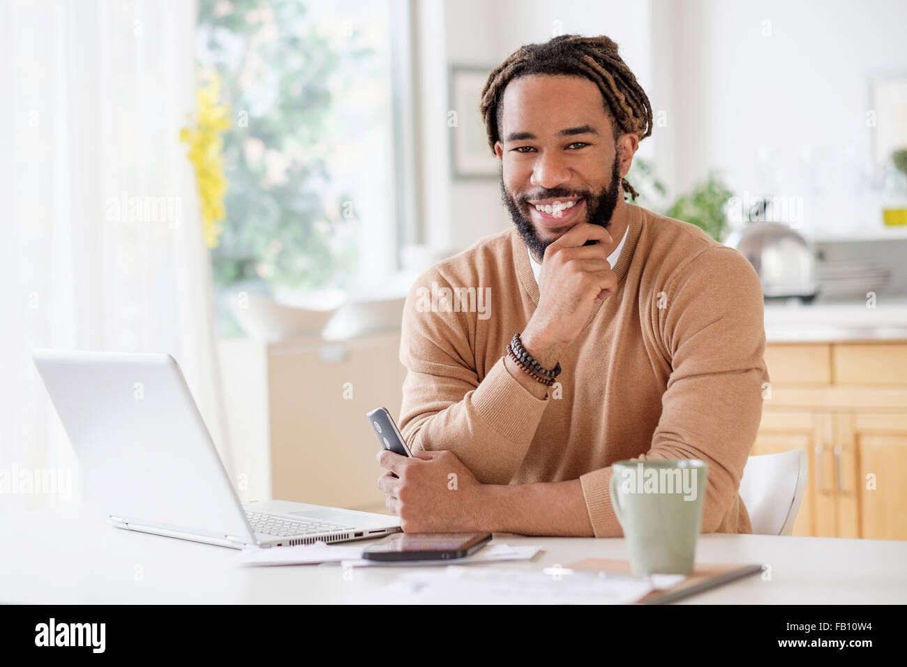 Portrait of smiley young man with laptop at table - Stock Image