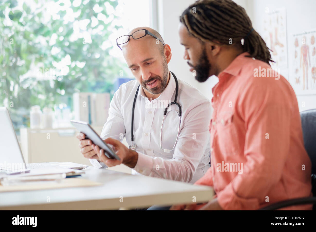 Doctor giving consultation to patient using digital tablet - Stock Image